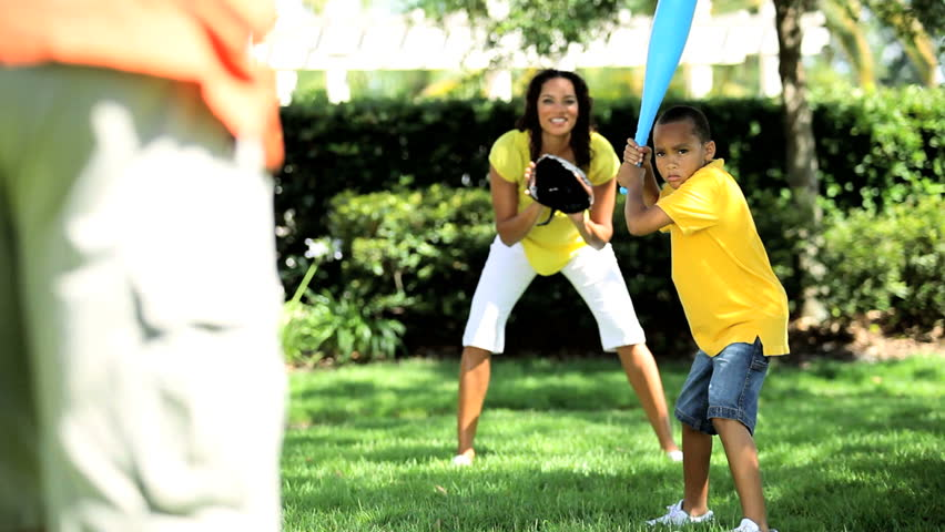 Young african american family playing baseball together in the park