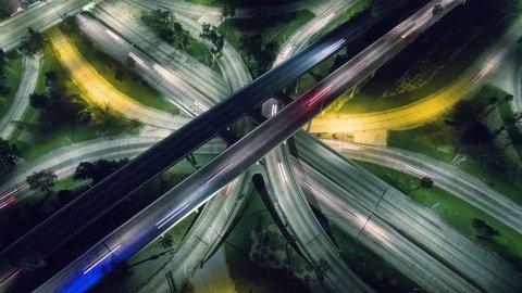 Vertical aerial view of traffic on freeway interchange at night. 4K UHD timelapse.