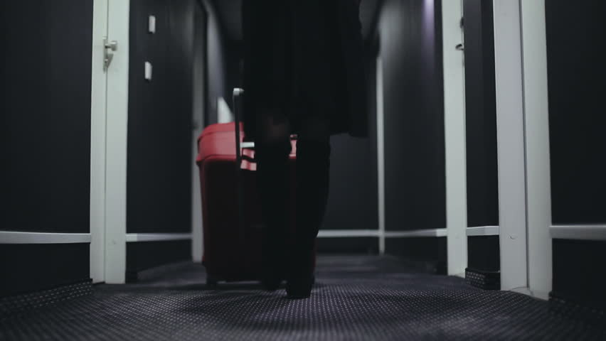 Asian woman in a long corridor of the hotel with a large red suitcase | Shutterstock HD Video #13051958