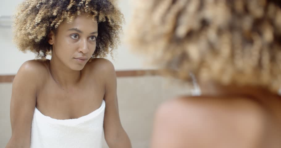 Young black woman checking her face in the mirror in bathroom | Shutterstock HD Video #13065776