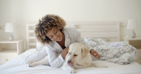 Young woman is holding a dog while laying on a bed in home