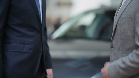 Young guy buying a car from a dealer. Handshake between buyer and seller. Car seller hands over the keys to the buyer.