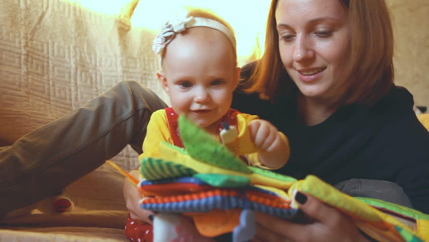 Beautiful young mother is reading fairy tale to her eleven month daughter