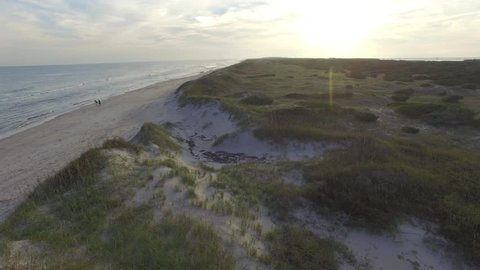 Low sunrise aerial shot flying over the dunes at Ocracoke Beach in North Carolina.