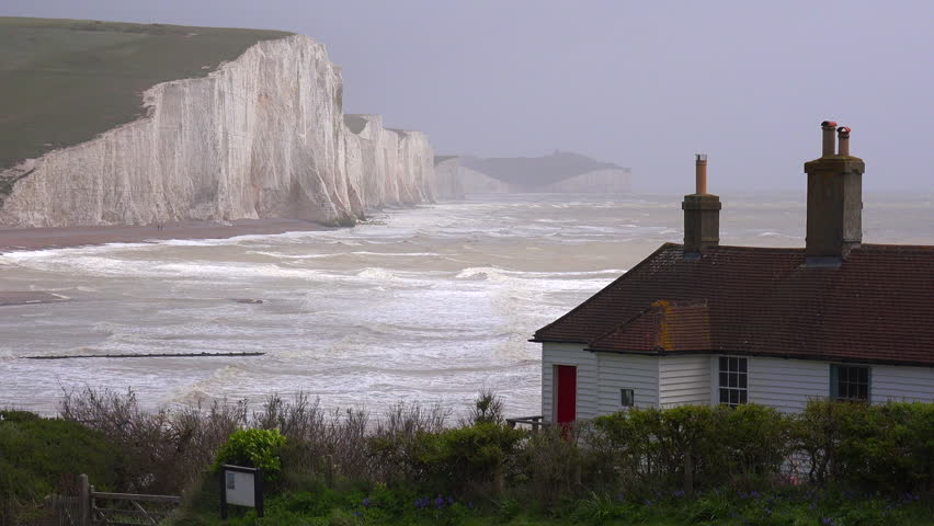 BEACHY HEAD, ENGLAND - CIRCA 2015 - Establishing shot of the beautiful houses along the shore of the White Cliffs of Dover at Beachy Head, England.