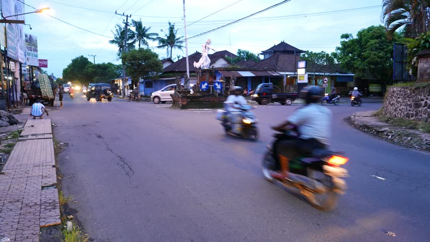 UBUD, INDONESIA - MARCH 13, 2015: Busy traffic at rural street intersection, dusk view, with sounds. Typical Asian traffic at the Jalan Raya Teges and Jalan Cok Rai Pudak intersection, near Ubud city