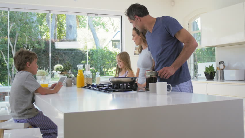 Young daughter walks into family kitchen in modern contemporary home while parents making healthy breakfast | Shutterstock HD Video #13159448