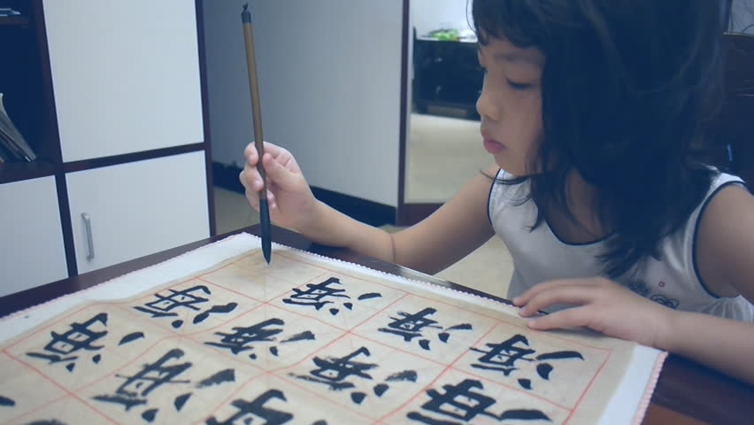 Asian kid writing with Chinese brush