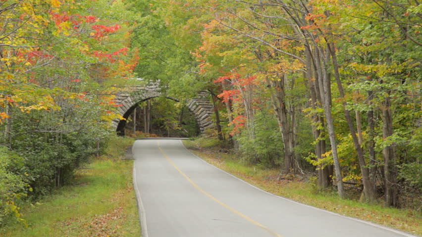 Two cars drive on a stone bridge on Park Loop Road, over Duck Brook Road, in Acadia National Park in Autumn.