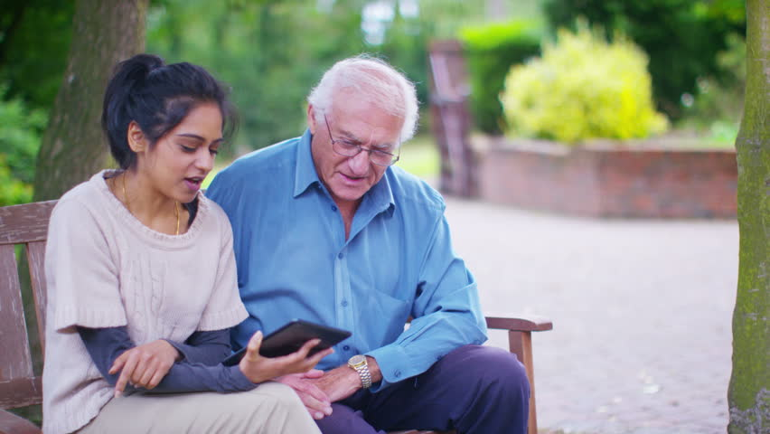 4K Caring young home support worker showing elderly gentleman how to use a computer tablet. Shot on RED Epic | Shutterstock HD Video #13175699