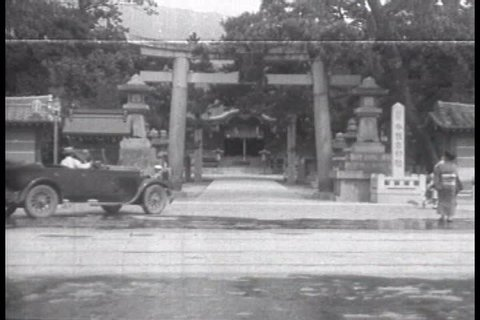 CIRCA 1920s - Japan, home to a General Motors Company facility, is shown with a Torii, a woman in a kimono, a man carrying with a carrying pole and general city scenes in 1927.