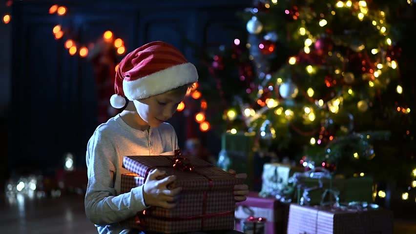 On Christmas Eve, a little boy open a gift in front of a decorated Christmas tree, he has expressions of joy and surprise, the atmosphere is warm. Special effects on video