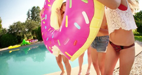 Laughing group of girl friends holding a pink donut novelty pool inflatable up in front of them like a photo frame outdoors in the sun