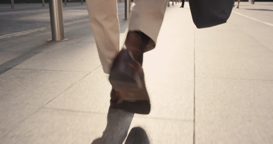 Close crop of businessman feet walking in city. Man commuting to work. Steadicam shot in slow motion with warm natural light on sidewalk | Shutterstock HD Video #13200020