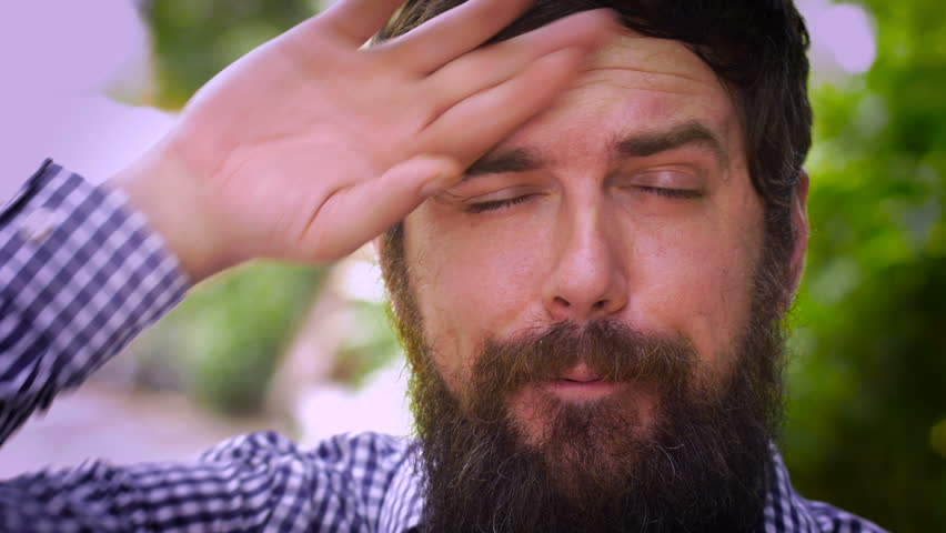Close up portrait of a young hipster man with a full beard letting out two different sighs of relief. He wipes his brow with each hand and smiles, relaxing after a stressed out event. | Shutterstock HD Video #13208108