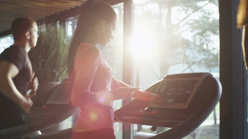Fit athletic caucasian girl is starting to run on the treadmill in sport gym with earphones. Shot on RED Cinema Camera in 4K (UHD).