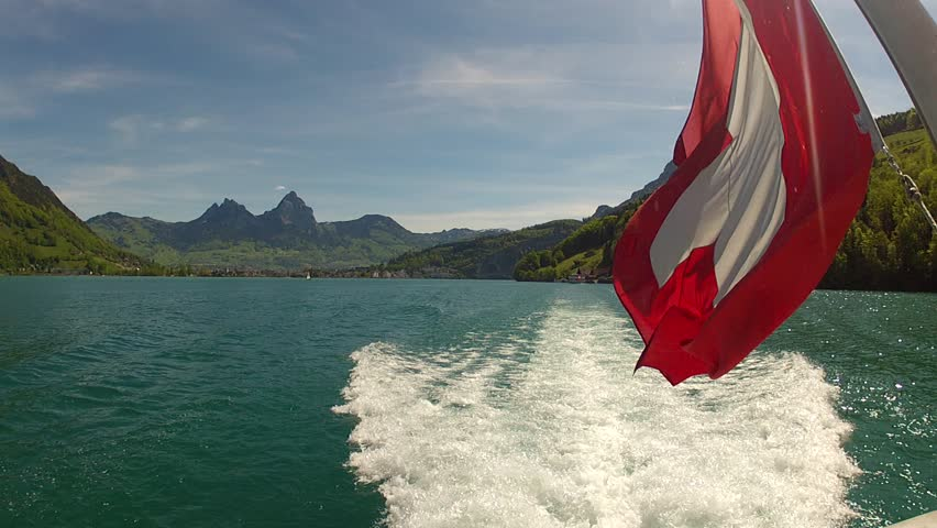 View at stern of cruise ship on Lake Lucerne, Switzerland with Mythen and Brunnen in background.