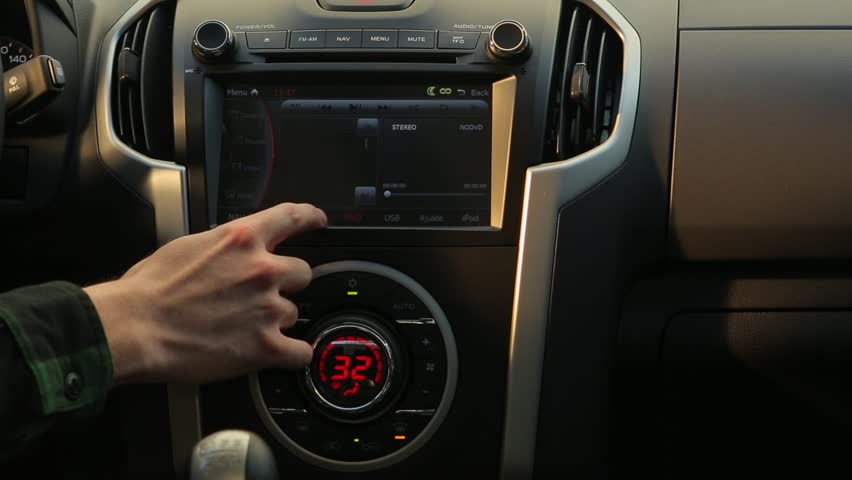 CAR INTERIOR - The camera pans to the right over the radio touch screen on a luxurious pickup truck dashboard while a hand activates a button on the screen. - Santiago, Chile, July, 2014
