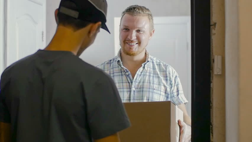 The courier gave a parcel to the customer. The man smiling broadly, took away a parcel and said goodbye to the courier. In slow motion