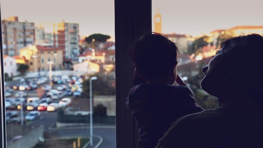 Mom and her little daughter looking out of the window. She discovers the world outside