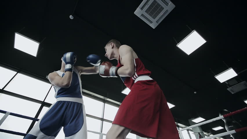 Two young professional boxers are fighting on the boxing ring