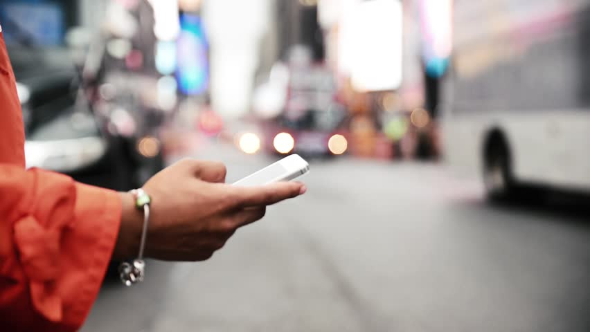 Woman using smart phone on the street. Time square traffic in the background
