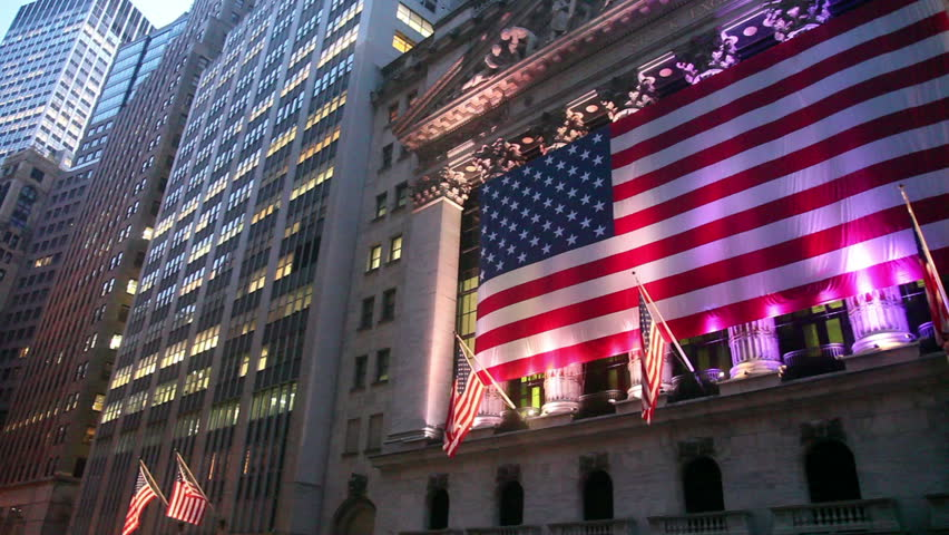 Iconic building of NYSE at dusk , with lights on