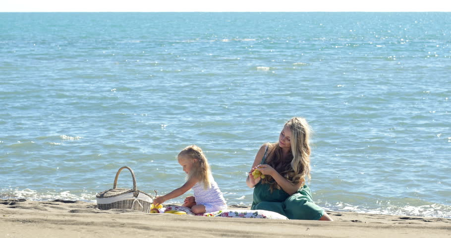 Mother and daughter at a picnic on the beach | Shutterstock HD Video #13298528