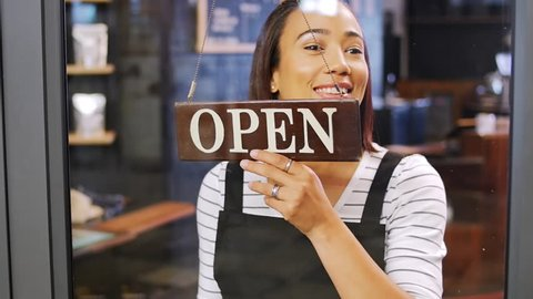 Cafe shop owner worker turning over open sign, happy and smiling first day of opening for small business