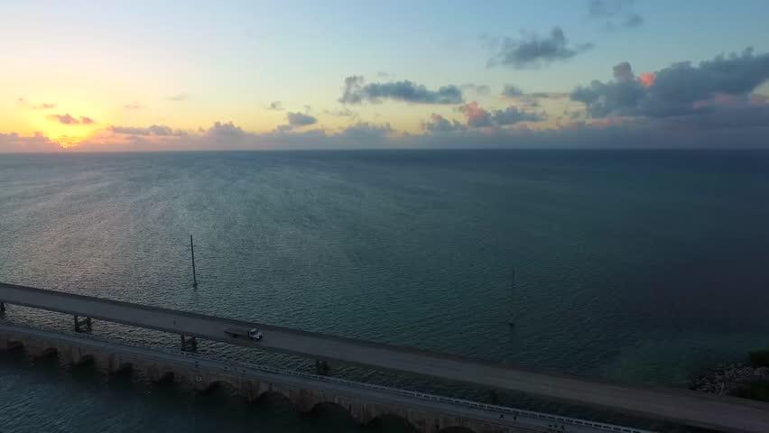 Aerial pan view at sunrise of ocean and Seven Mile Bridge on Overseas Highway in Florida Keys