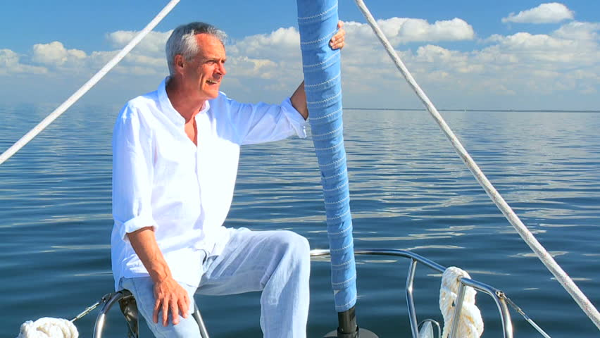 Successful retired male enjoying leisure aboard his luxury sailing boat filmed at 60FPS