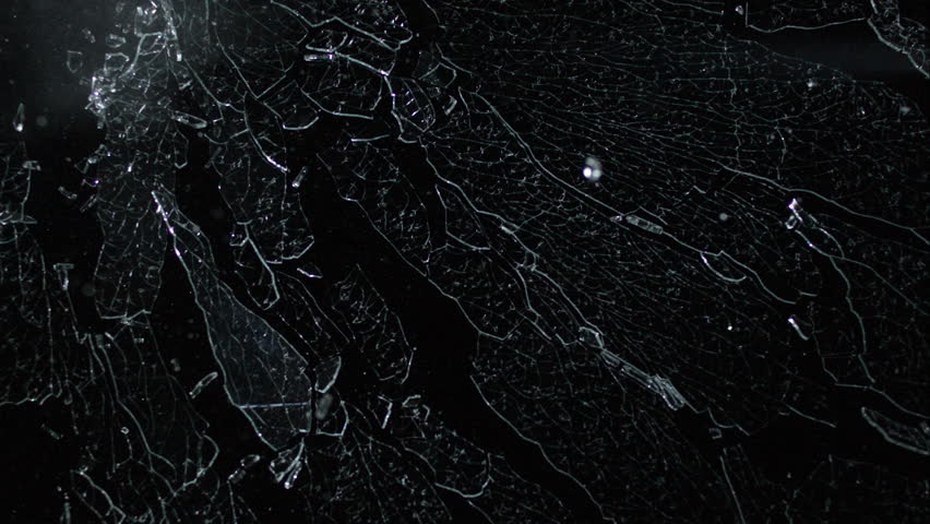 Tempered glass spiderwebbing and shattering isolated on black breaking in slow motion in 4k