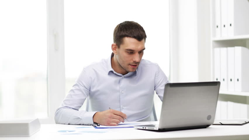 happy young businessman reading paperwork at desk in