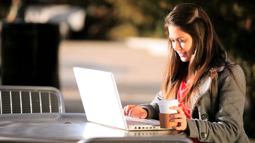 Young female student drinking coffee while working on her laptop computer outdoors