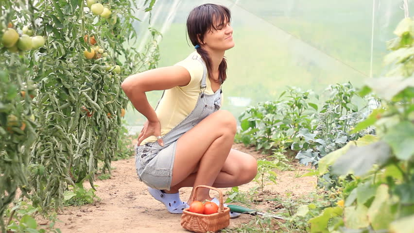 Woman having back pain while working in the garden, dolly shot