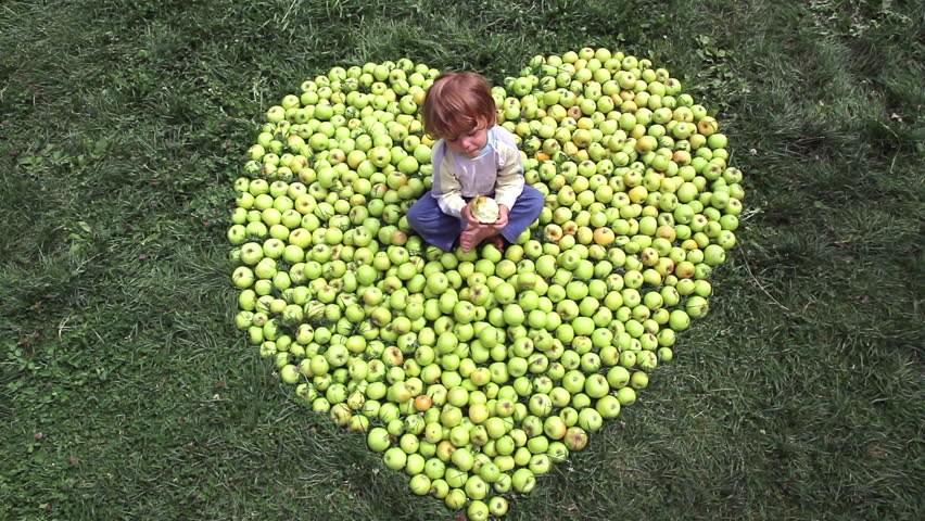 A little boy sits among apples folded into the shape of heart
