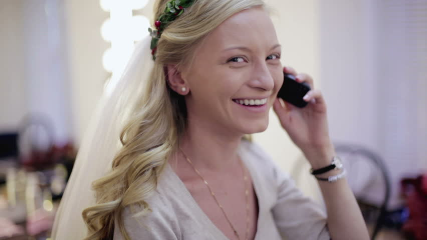 Bride speaks by the mobile phone and smiles. NTSC | Shutterstock HD Video #13357595