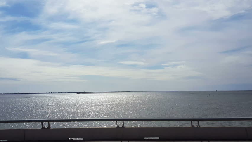 130536S-POV-passenger side window driving causeway to Galveston with sun light reflecting on the water of Galveston channel #13364768