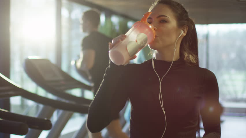 Attractive caucasian girl is drinking a protein shake drink next to a treadmill in the sport gym. Shot on RED Cinema Camera in 4K (UHD).