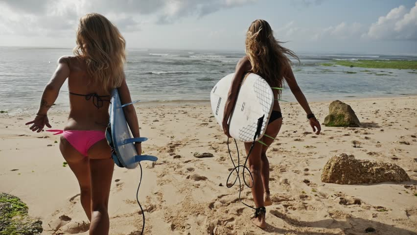 Two girls running into the ocean with their surfboards. Shot taken by a handheld gimbal in 50FPS.