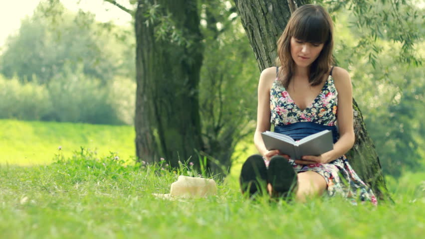 Young attractive woman reading book by the tree in park, dolly shot