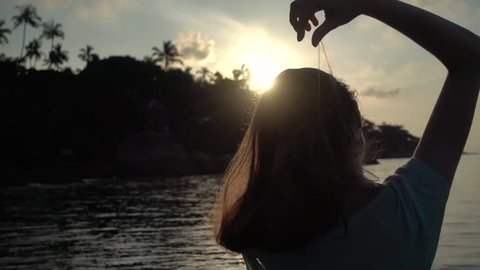 Girl smoothes her hair on a beach at sunrise