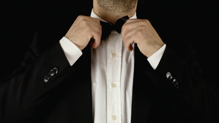 A well-dressed man adjusting his bow-tie.