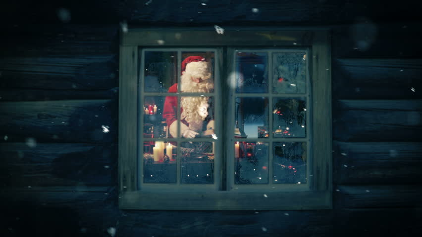 Santa seen through the frozen window preparing gifts for kids. Snowing.