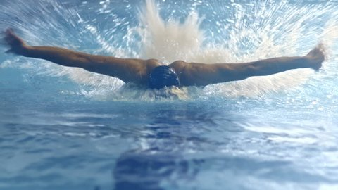 Shot from Front Side of Professional Swimmer Performing Butterfly Stroke during Training in Swimming Pool. Shot on RED Cinema Camera in 4K (UHD).