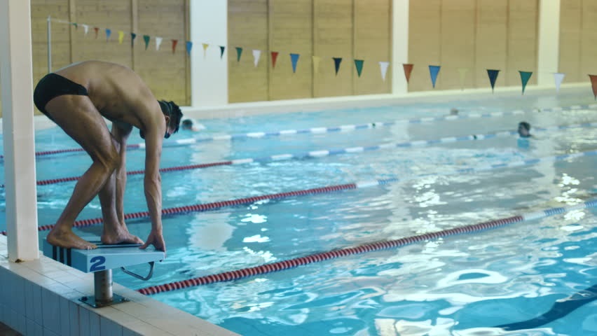 professional male swimmer jumping off the starting block and performing the butterfly stroke camera follow - Olympic Swimming Starting Blocks