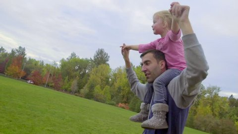 Dad spins around with little girl on shoulders and she loves it