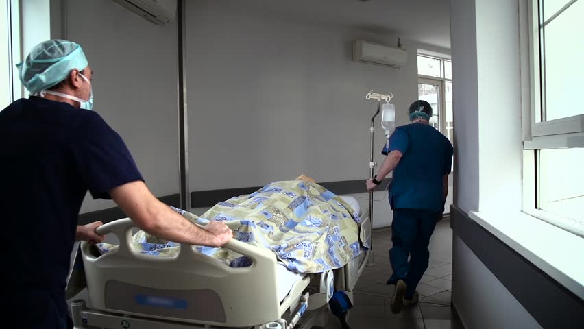 Patient on stretcher pushed at speed through a hospital corridor by doctors. In cart lies the educational dummy.