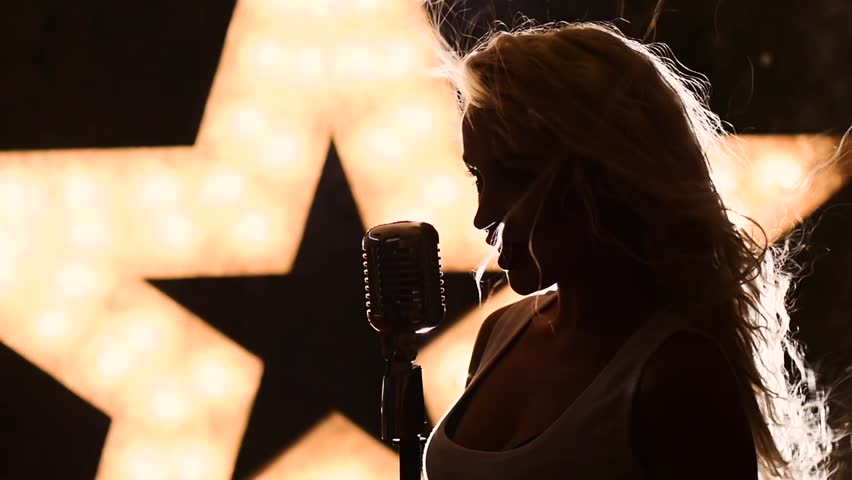 Singing Woman with Retro Microphone. female jazz singer with microphone, music hall, the scene, shining star in the background, slow motion, close up, silhouette