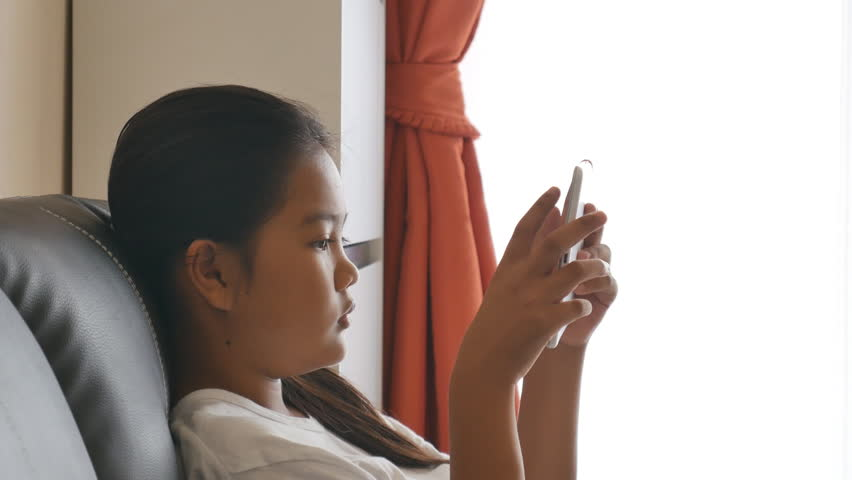 Young Asian lady to relaxing with tablet on sofa in the living room   Shutterstock HD Video #13500353